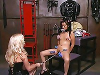 An Asian girl in pigtails takes clothespins and a riding crop all over her legs