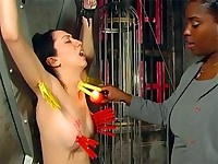 Girl is clamped and singed by hot wax