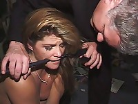 A man lashes a girl with a wide leather paddle, clutching her head between his knees, and touches her pussy