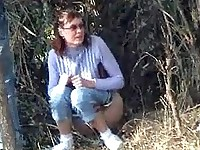 Lady in glasses pees under a tree being unsuspecting of cunning spying