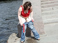 Bubbied slut in a red tank top and jeans urinating riverside in summer