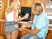 A blonde girl and a guy are in the kitchen kissing each other. She licks his crotch and he takes her clothes off. After she has sucked his dick for a while she lies down on some chairs to be fucked and then they end up on the floor.