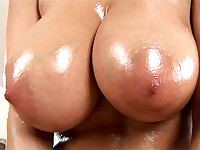 Pornographic bitch with big chest rubs her vagina and boobs with oil.