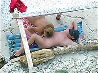 A nudist couple enjoys having oral sex on a beach where voyeurs spy
