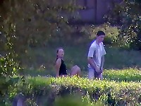 A clothed couple enjoying sex in the grass under spycam supervision