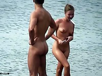 Naked chick brushing teeth and chilling on the beach with other nudists